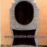 Памятник из серого камня с полукруглой аркой