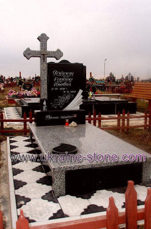 Памятник из черного камня с большим крестом